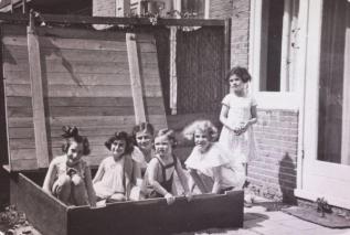 Ana Frank jugando en una caja de arena con amigas, en mejores tiempos.